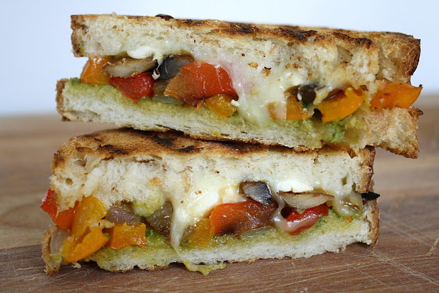 Roasted vegetable panini with pesto cut in half and stacked on a cutting board