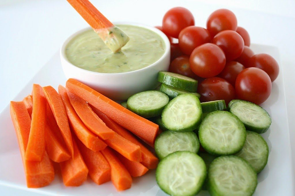 Plate of carrots, cucumbers, and tomatoes for dipping into creamy avocado dressing