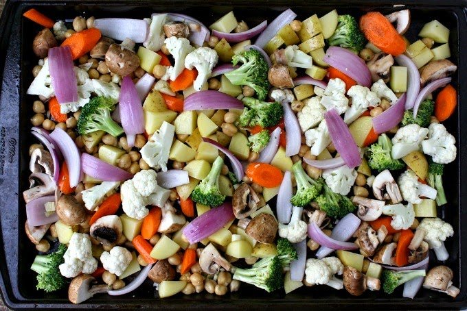 Sheet pan of assorted raw vegetables waiting to be roasted