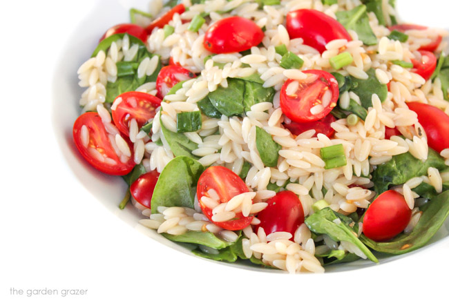 Bowl of orzo salad with spinach and tomato
