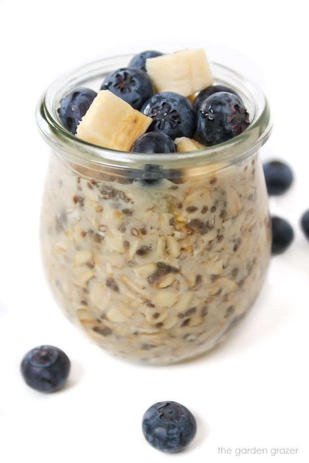 Small jar of vegan overnight oats topped with banana and blueberry