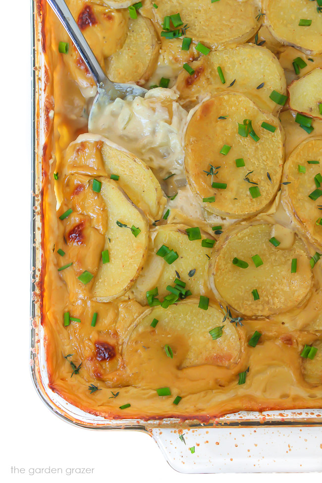 Pan of vegan scalloped potatoes with a spoon